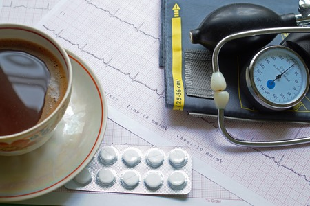 cuff: Blood pressure cuff, pills, cup of coffee, and ECG results on the table