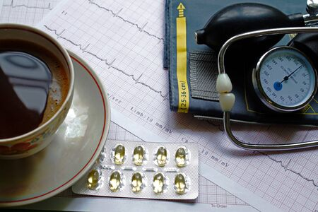 cuff: Blood pressure cuff, cup of coffee, and ECG results on the table Stock Photo