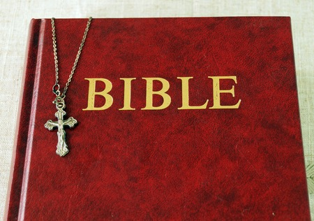 gutenberg: Red Bible book and a metal cross with Jesus on a chain Stock Photo
