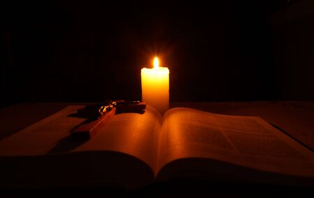 gutenberg: Burning candle,  open Bible and crucifix on desk in dark. Stock Photo