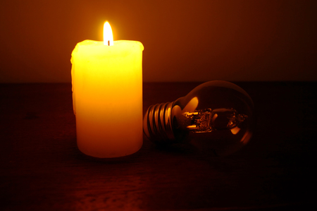 Burning candle and lamp on desktop in darkness (no electricity) Stock Photo