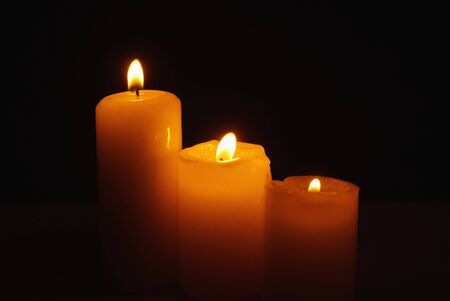 three objects: Three burning candles in the darkness (three objects)