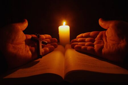 gutenberg: Burning candle, open Bible and prayer hands in the darkness. Stock Photo