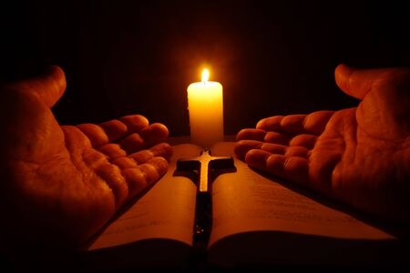 Burning candle, open Bible and prayer hands in the darkness. Stock Photo
