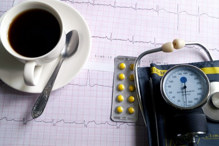 Hemopiezometer for measuring blood pressure, cup of coffee, pills and ECG test results on the table