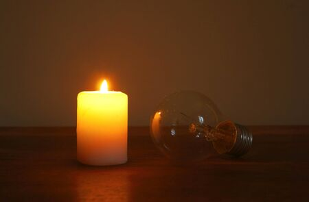 Burning candle and lamp on desktop in darkness (no electricity). Troubles with electricity after storm.