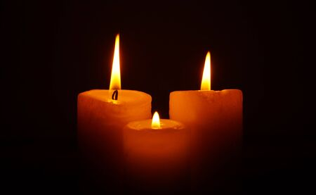 mournful: Three burning candles in the darkness. Mournful fire of candles. Fire of sorrow. Tragic state.