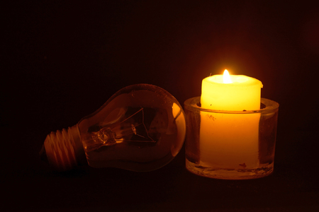 Burning candle and lamp on desktop in darkness (no electricity) Stockfoto