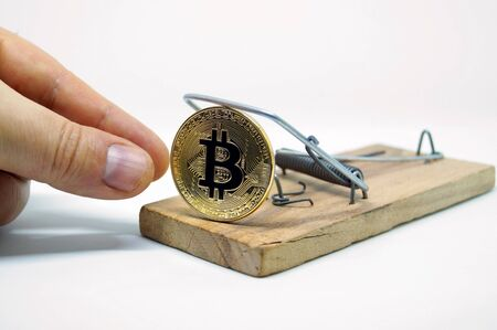 A hand that takes a coin of bitcoin from mousetrap. Risks and dangers of investing in the crypto currency. Stock Photo