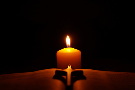 Burning candle,  open Bible and crucifix in the dark. Copy space for evening pray or biblical verse. Selective focus.
