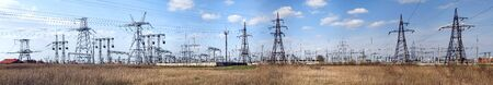 Panoramic image of high voltage substation. Distribution electrical power. Ukrainian oblenergo sale. Silhouettes of pylons and towers.