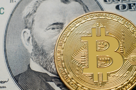 A symbolic coins of bitcoin on banknotes of fifty dollars close-up. Exchange bitcoin cash for a dollar.
