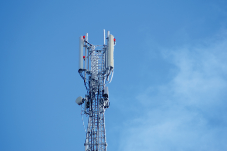 Communication tower or 3G 4G network telephone cellsite silhouette on blue sky and space for text. Frozen equipment
