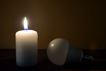 Burning candle and lamp on desktop in darkness. Broken electrical wires via storm. Electricity missing. Blackout.
