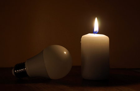 Burning candle and lamp on desktop in darkness. Broken electrical wires via storm. Electricity missing. Blackout concept.