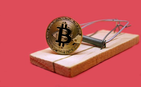 Mousetrap with gold bitcoin on red background. Risks and dangers of investing to bitcoin. Soap bubble of crypto currency.