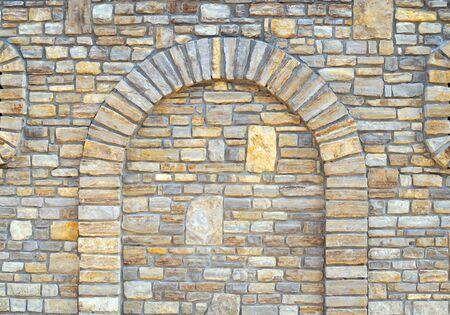Fond de mur de pierre avec arch. Voûte murée dans un fond de mur de pierre.
