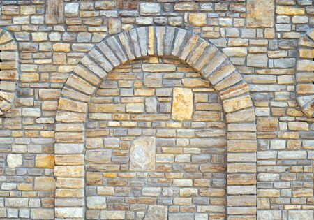 Stone wall background with arch. Walled-up archway in a stone wall background.