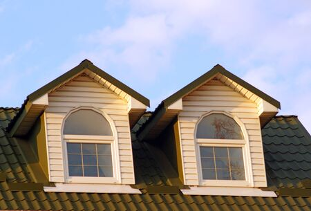 The pair of windows look out from steep roof to blue skies. Two attic windows with white frames on the roof of red tiles. Stockfoto
