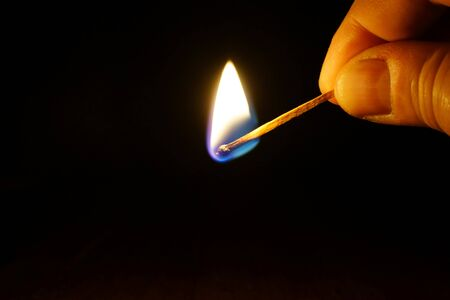 Burning match in a hand on black background.