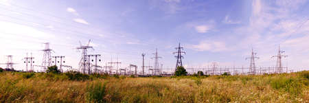 Panoramic image of high voltage substation. Distribution electrical power. Silhouettes of pylons and towers. Stock Photo
