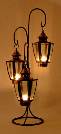 votive: Three glowing copper votive lamps on stand