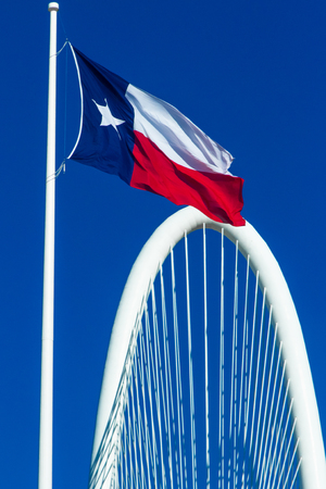 Texas flag waving over Margaret Hunt Hill Bridge.