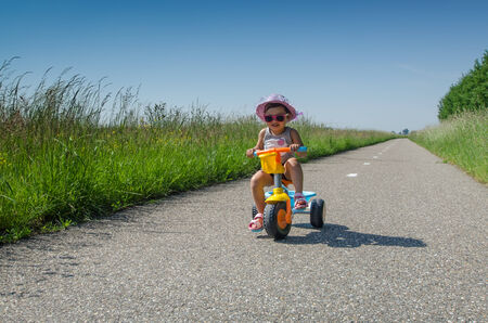 three wheeler: Young girl on three wheeler on long road  Stock Photo