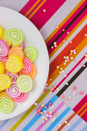 a swirly candy on the plate with colorfull background (portrait)
