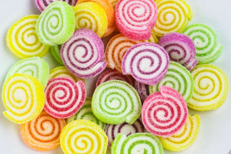 a close up swirly candy on the plate with colorfull background
