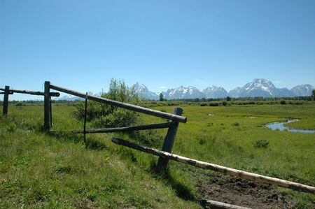 An old fashioned wooden log fences separates a green mountain meadow in Wyoming. photo