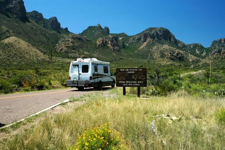 A small recreational vehicle navigates past a bear and mountain lion warning in big Bend National Park. Stock Photo - 998780