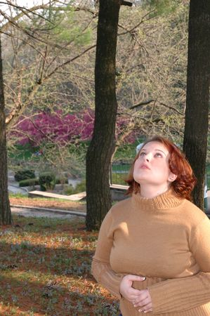 A young girl looks up into the forest canopy with a pensive expression.