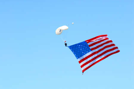 The American flag trails a patriotic skydiver. Stock Photo - 1133656