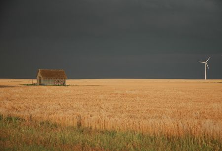 An old shack sits across from a modern wind farm in south Kansas.