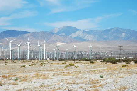 A large windfarm in the southern California Mojave desert with blue sky and mountains in the background. Stock Photo