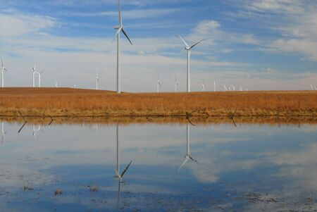 Several turbines from a Kansas wind farm are reflected in a small natural pond.