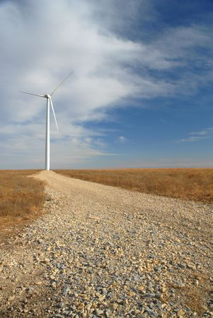 A gravel road leads up to a large white wind turbine. Stock Photo