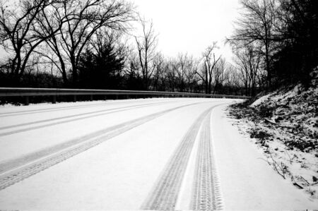 A black and white image of tire tracks made on a snowy road with snow still falling.