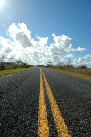 contrasty: A street shot from the middle of the road with a bright blue sky and contrasty white clouds. Stock Photo
