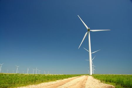 A gravel service road leading to a large wind turbine in a Kansas windfarm.