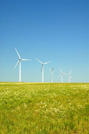 A line of energy producing wind turbines in a green field. Stock Photo