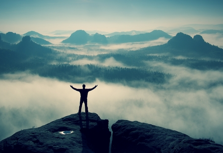 boy  naked: Gesture of triumph. Happy hiker in black.  Tall man on the peak of sandstone rock in national park Saxony Switzerland watching down to landscape. Stock Photo
