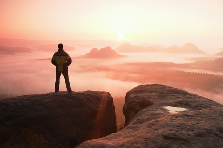 empires: Moment of loneliness. Man on the rock empires  and watch over the misty and foggy morning valley.