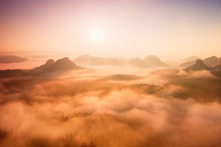 foggy hill: Red daybreak. Misty daybreak in a beautiful hills. Peaks of hills are sticking out from foggy background, the fog with red and orange due to Suns rays.