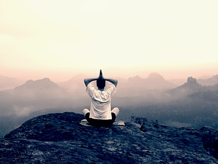 yoga rocks: Man is doing Yoga pose on the rocks peak within misty morning