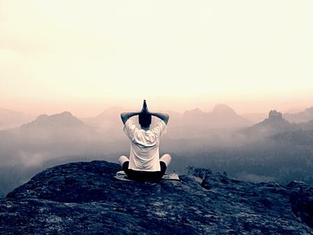 yoga rocks: Man is doing Yoga pose on the rocks peak within misty morning