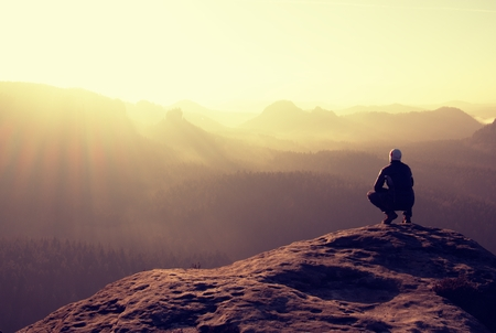 horizon: Hiker sits on a rocky peak and enjoy the scenery