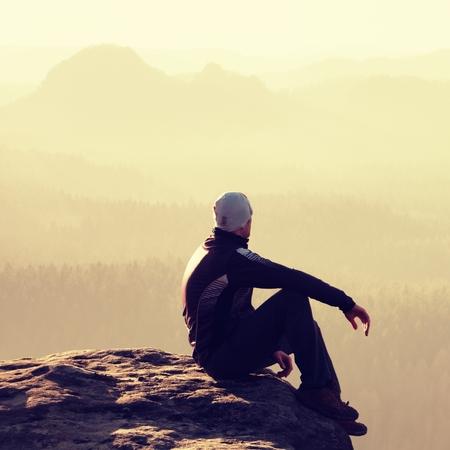 rocky peak: Hiker sits on a rocky peak and enjoy the scenery
