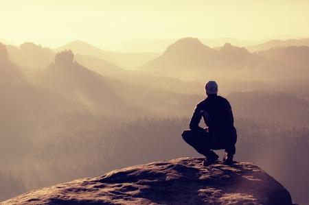 personas mirando: Hombre joven en ropa deportiva negro está sentado en el borde del acantilado y mirando a Misty Valley abajo